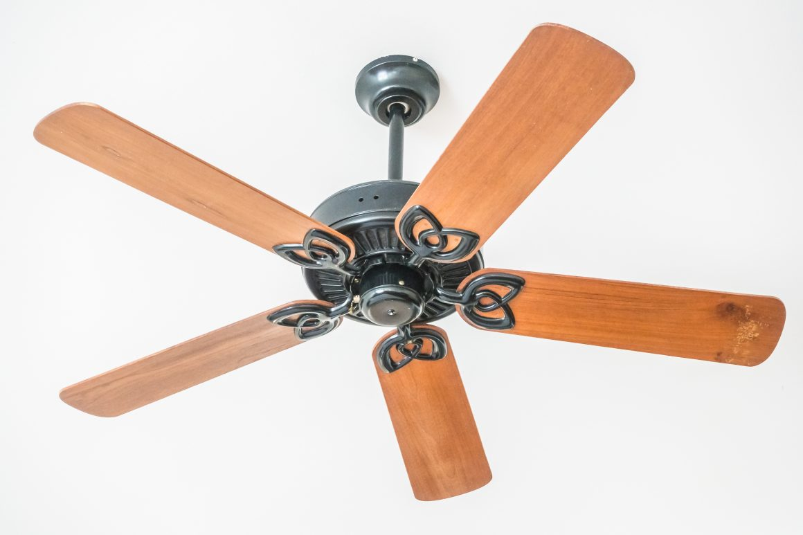 Up close view of a wood blade ceiling fan with metal accents, installed