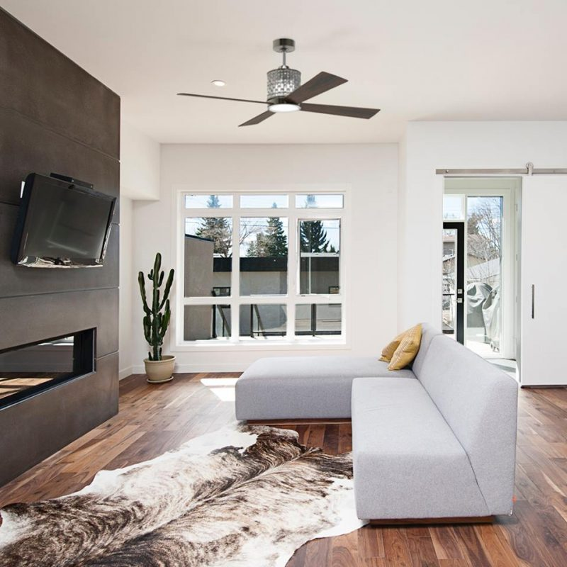 Modern metal and wood ceiling fan in a contemporary living space with tv and white couch