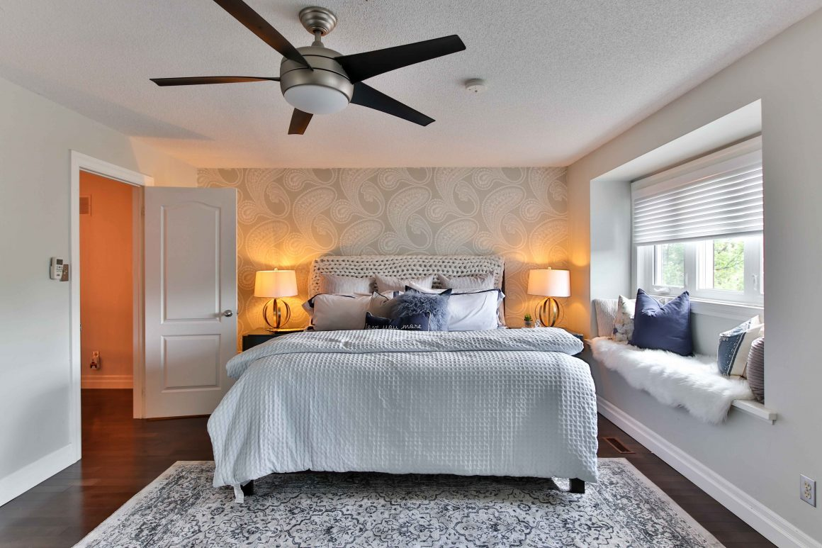 Modern brushed silver style fan with frosted light fixture in clean, modern, white bedroom