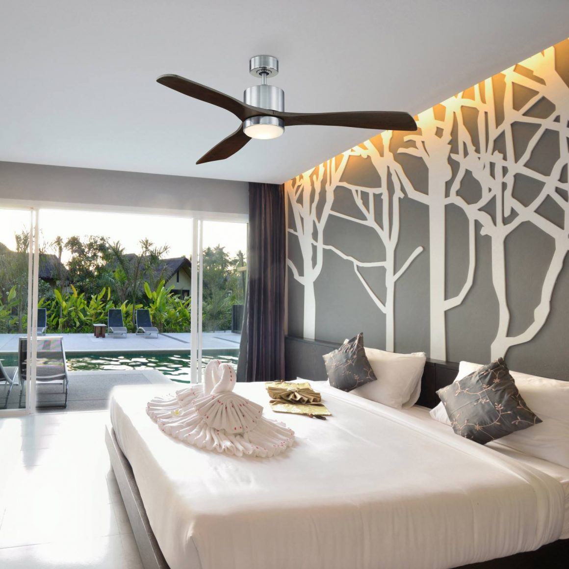 A contemporary bedroom with mid-century modern ceiling fan and large windows facing the swimming pool
