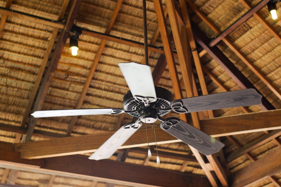A dark wood rustic ceiling fan hanging from natural ceiling