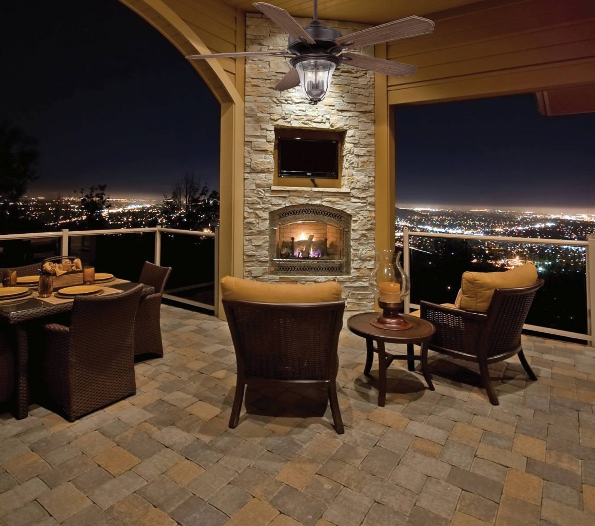 A beautiful backdrop of  a backyard patio with outdoor furniture and city lights in the background