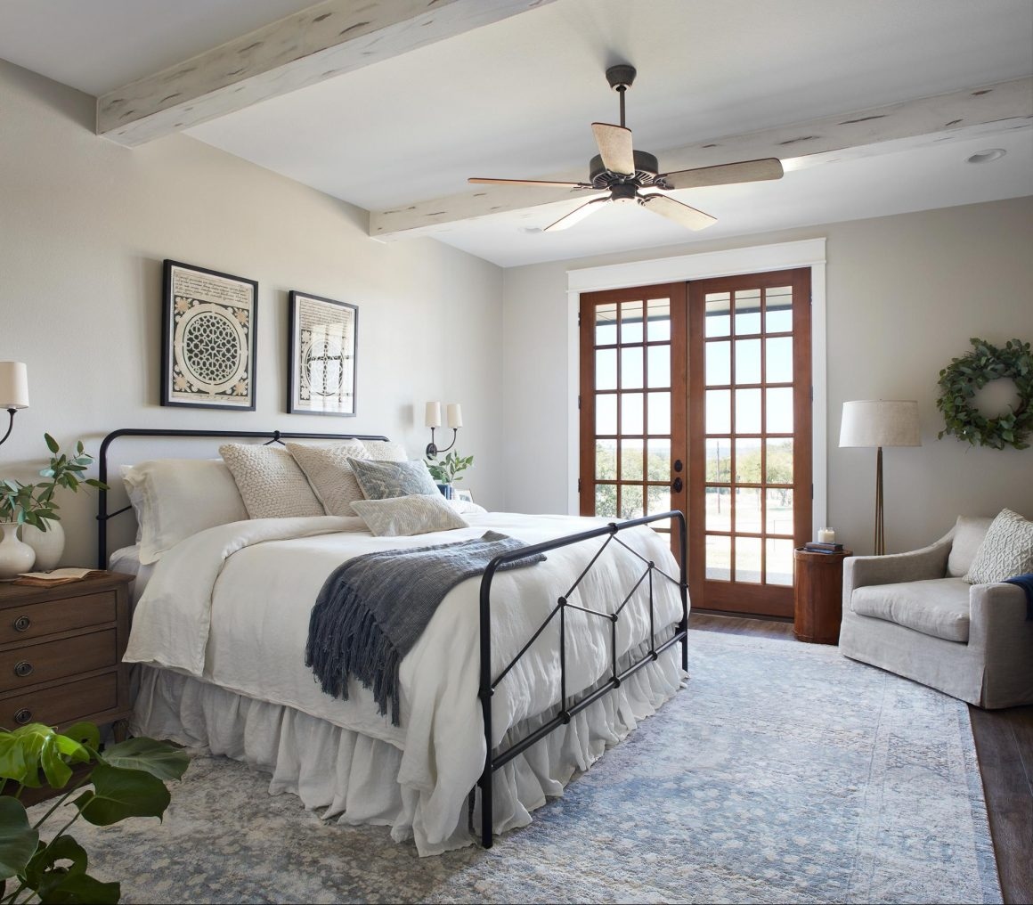 A neutral-colored bedroom with different textures and natural light seeping through