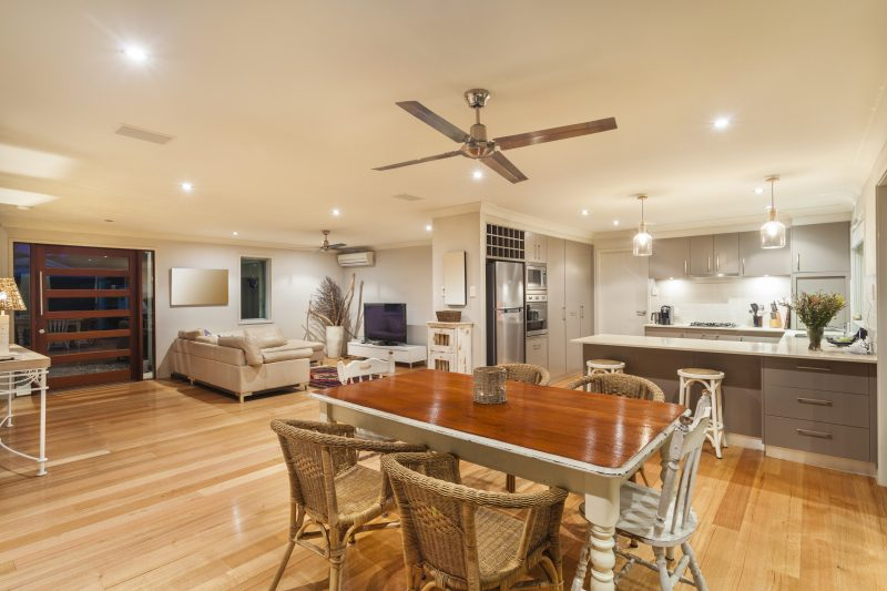 Sleek, four-blade ceiling fan in neutral kitchen; utilizing ceiling fan switch for cooling and warming