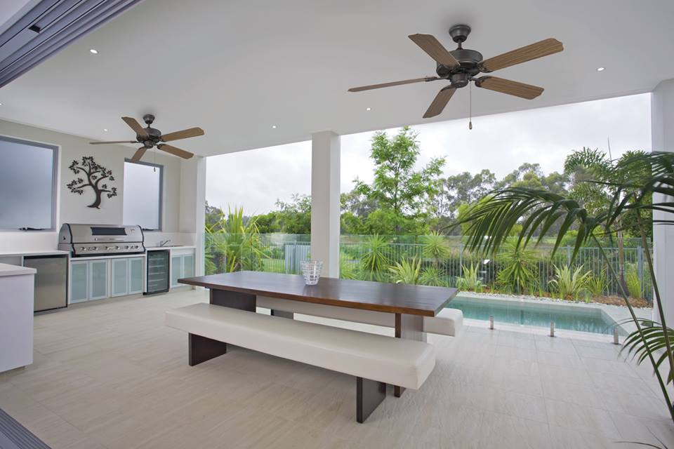 Backyard patio with two outdoor ceiling fans and a pool and tropical trees in the background
