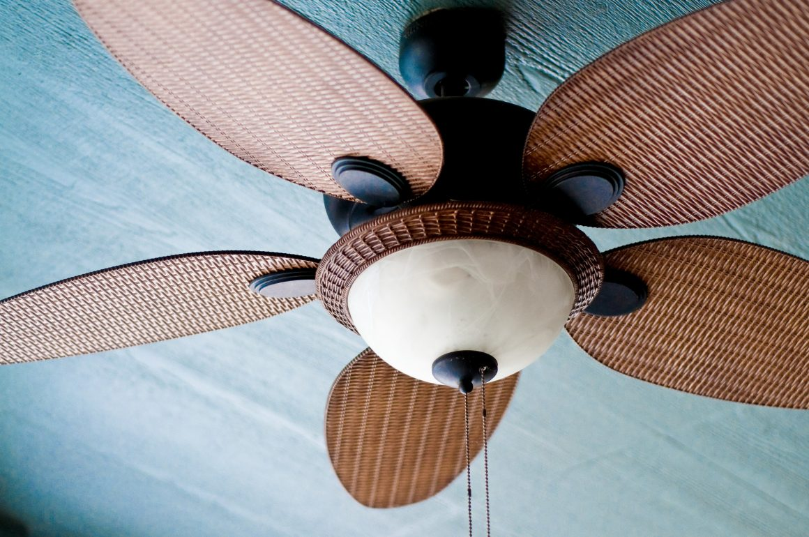 A closeup view of rustic ceiling fan blades made of wicker mounted on a blue ceiling