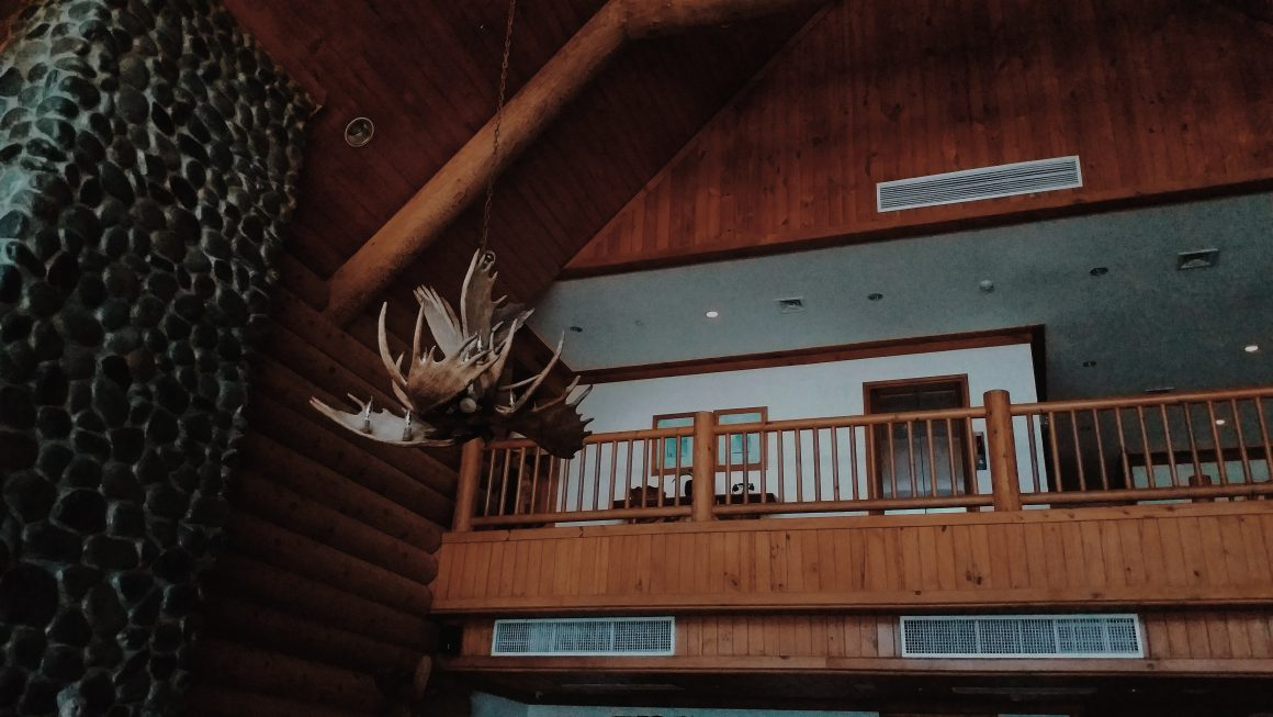 A dark wood lodge featuring a ceiling fan made from antlers