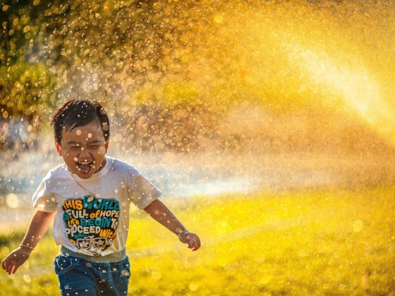 Smiling child playing in sprinklers on grass as an example of a way to improve your mood